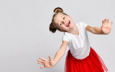 Portrait of happy smiling kid girl in red fatin skirts and white t-shirts standing holding out hands to us having fun, playing dancing at the party celebration on white Archivio Fotografico - 134732738
