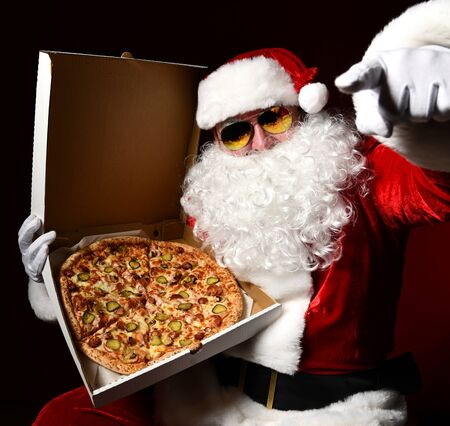 Santa Claus in sunglasses is holding a box with big hot tasty sliced pizza, pointing finger at us, choosing on dark red background. New year and Merry Christmas fast food concept