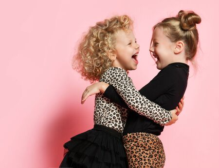 Two happy kids girls best friends sisters in leopard print clothes pants and sweater are hugging looking at each other laughing having fun on pink background