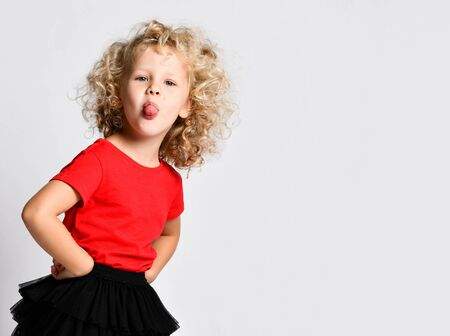 Frolic little kid girl in black fatin skirts, red t-shirts is standing holding hands on hips, sticking her tongue out at us, teasing, having fun, playing on white with copy space