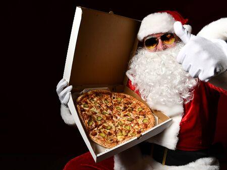 Santa Claus in aviator sunglasses is holding a box with big hot tasty sliced pizza, showing thumb up gesture on dark red background. New year and Merry Christmas fast food concept