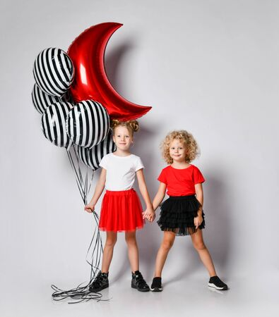 Happy kids girls in red and black skirts and white and red t-shirts are standing together holding hands waiting celebrating having fun at party with stylish air balloons on white