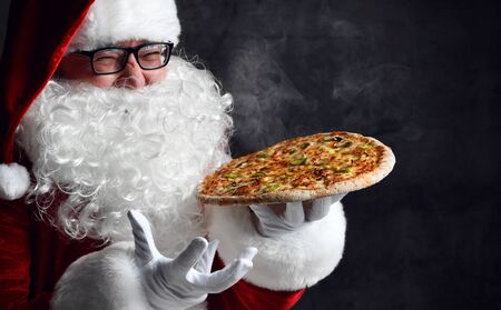 Happy laughing Santa Claus is holding big hot steaming pizza, offering us. New year and Merry Christmas and happy holidays concept
