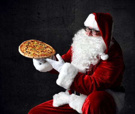 Happy and generous Santa Claus is holding steaming slice of hot pizza eating. New year and Merry Christmas fast food concept Stock fotó