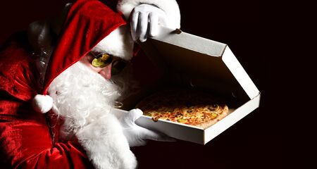 Santa Claus in sunglasses lifting the pizza box lid and peering inside, watching, desiring, going to steal a slice piece. New year and Merry Christmas fast food concept banner Stock Photo