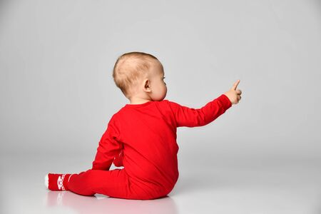 Little toddler boy points finger up side in red infant bodysuit with free text space on gray background