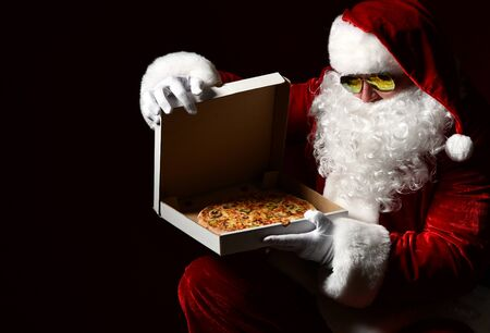 Santa Claus is opening closing pizza box, looking inside, desiring, going to take a slice, packing gift on black with copy space. New year and Merry Christmas fast food concept