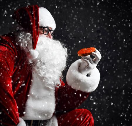 Santa Claus is holding red salmon caviar sandwich, looking at it going to eat under the snow on dark background. New year and Merry Christmas and happy holidays concept Stockfoto