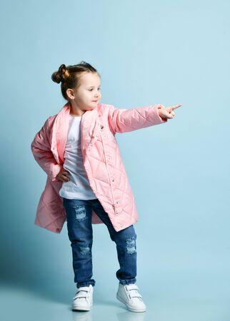Stilvolles fröhliches, ausgelassenes kleines Mädchen mit lustigen Brötchen und im weißen T-Shirt der Winterjacke, moderne blaue zerrissene Jeans zeigt ihren Finger beiseite