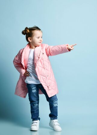 Stylish happy frolic little kid girl with funny buns and in winter jacket white t-shirt, modern blue torn jeans is pointing her finger aside