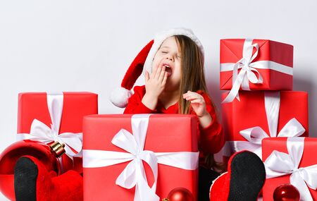 Cute little kid girl in red sweater, red cap and felt boots is sitting surrounded by Christmas gifts presents red boxes with ribbon, waiting, yawning, waking up, dreaming on white Stock Photo