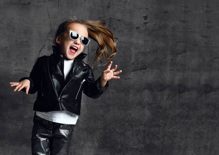Cheerful screaming kid girl frolic in leather jacket, jeans and sunglasses is playing having fun singing rock heavy metal songs dancing jumping on dark concrete wall background