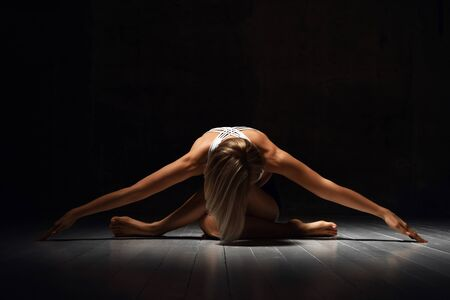 Beautiful athletic girl trainer doing yoga pose stretches in sport fitness gym club