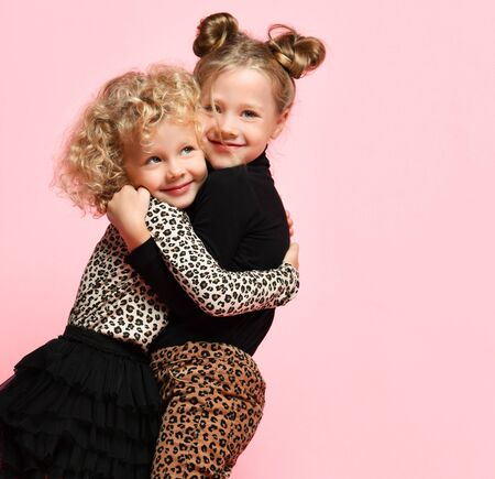 Two happy nice kids girls best friends sisters in leopard print clothes pants and sweater are hugging smiling feeling love on pink
