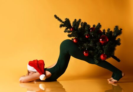 Beautiful sporty girl in a New Year hat does yoga  stretching exercise holds and carry decorated Christmas tree.
