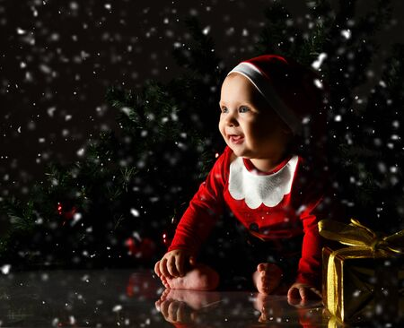 Infant  boy  in red christmas cap and costume is sitting at golden New Year gift box present with ribbon and bow