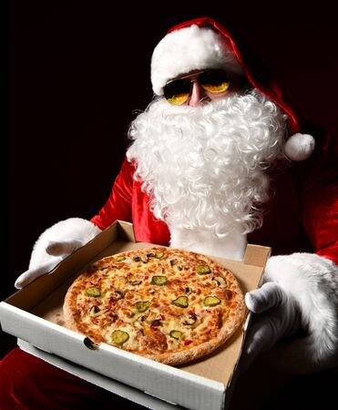 Santa Claus in aviator sunglasses is holding big tasty pizza in opened box showing brought giving us on dark background. New year and Merry Christmas fast food concept