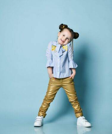 Cool little baby kid girl with funny buns and in blue shirt and gold leather pants is posing with her hands in pockets