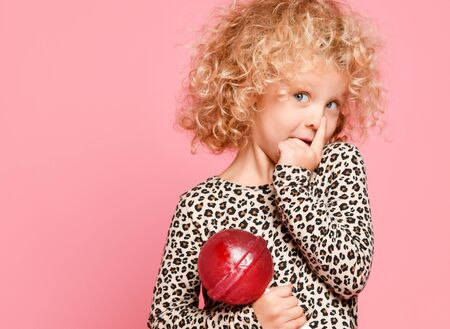 Cute blonde kid girl with curly hair in leopard print sweater is posing with big lollipop, holding her finger at nose on pink
