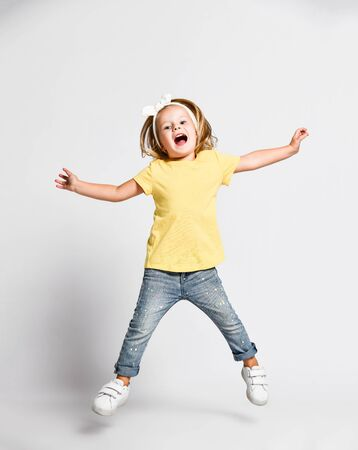 Active cheerful happy kid baby girl blonde in yellow t-shirt, blue jeans and sneakers is jumping high