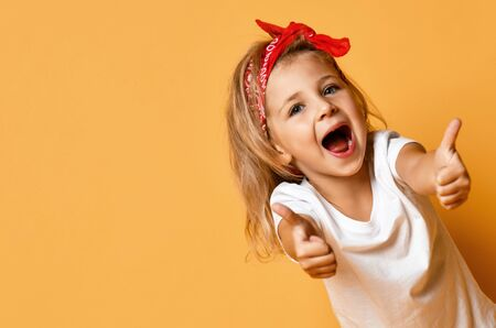 Happy screaming popped up blonde kid girl in white t-shirt and red headband is showing thumbs up gesture with both hands at free copy space on yellow background