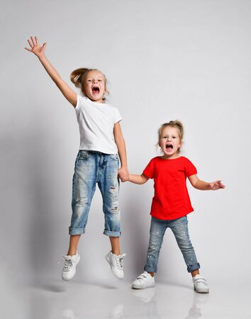 Two happy screaming funky kid girls in jeans and t-shirts friends sisters are playing jumping with hands up having fun. Stock fotó