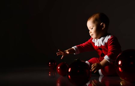 Smiling baby boy toddler in santa claus costume playing with christmas tree red glass balls rolling on the floor catching on dark Stock Photo