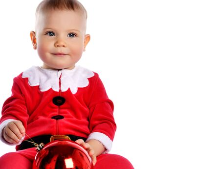 Little child boy toddler in santa claus christmas costume and hat happy smiling with red gift ball