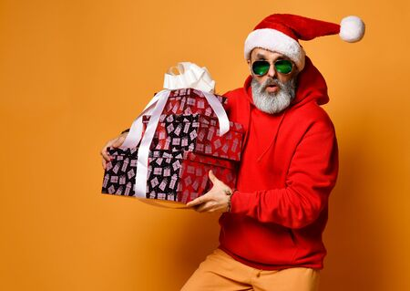 Popular elderly man or mature old men in a Santa Claus hat and sunglasses happy walks with New Year's gifts hurry for xmas party on a yellow background