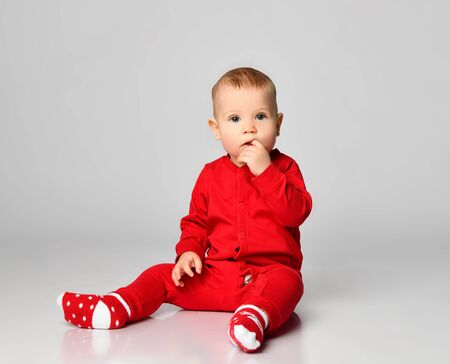 Little toddler boy in red infant bodysuit is sitting on the floor looking puzzled with interest touching his mouth with free text space on gray full body Zdjęcie Seryjne