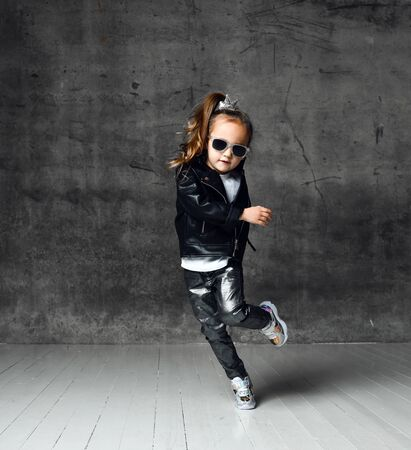 Cool frolic kid girl in leather jacket, jeans and sunglasses is having fun modern dancing playing running having fun on dark concrete wall background