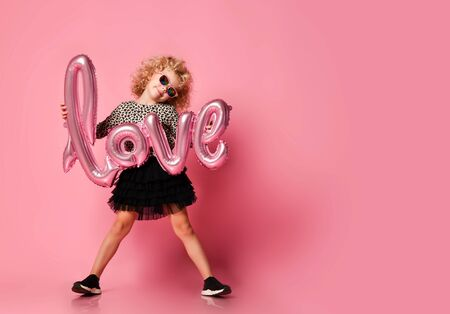 Happy smiling blonde kid girl with curly hair in leopard print shirt and  skirt is posing with love word air balloon on pink