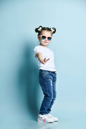 Cool cute little baby kid girl with funny buns and in sunglasses, white t-shirt and blue jeans is showing V victory sign gesture on background