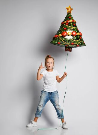 Little kid girl in jeans, t-shirt with christmas tree