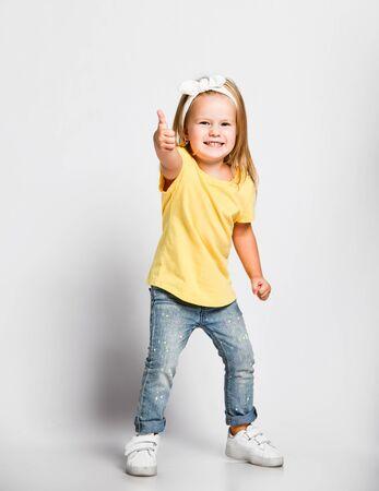 Sorridente bambino malizioso bambina bionda in maglietta gialla e jeans blu