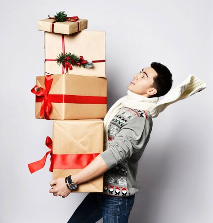 Young handsome guy is in a hurry for a Christmas dinner with a bunch of New Year's red gifts. 版權商用圖片