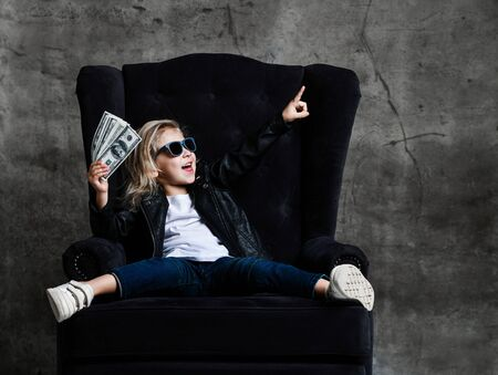 Happy smiling rich kid girl millionaire sitting in expensive armchair with a bundle of money dollars and euro cash bills show winning sign with hand fist screaming on dark background Zdjęcie Seryjne