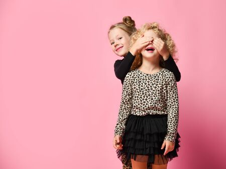 Two kids girls friends sisters in leopard print clothes pants and shirt are playing Guess Who game Banque d'images
