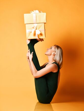 Smiling sporty girl does yoga  stretching exercise holds New Year Christmas gifts boxes presents on her upturned legs feet
