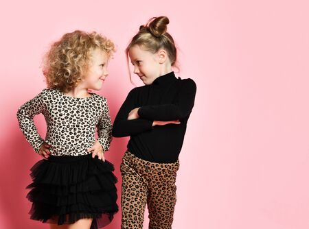 Two happy cool kids girls best friends sisters in leopard print clothes pants and sweater are looking at each other