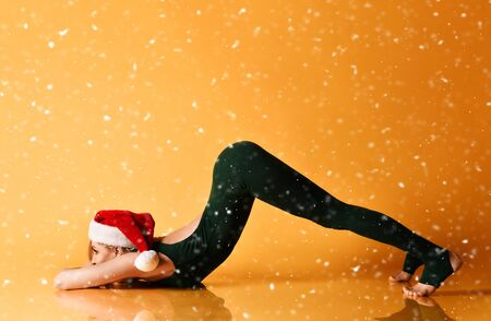 Young slim woman girl in a New Year christmas hat does yoga asana stretching exercise under the snow. Stock Photo