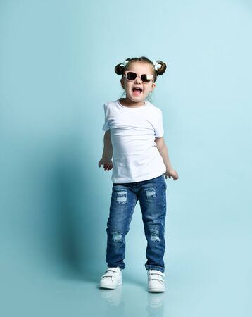 Joyful frolic smiling little baby kid girl with funny buns with bows and in sunglasses, t-shirt and blue jeans is dancing, playing, singing, shaking hips Stock Photo