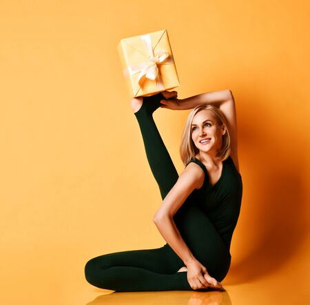 Happy smiling calm athletic woman does yoga asana stretching exercise holds New Year Christmas gift box on her upturned leg foot. Healthy life fitness concept on yellow background Stock Photo