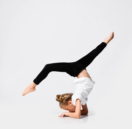 Slim athletic blonde kid girl is doing gymnastic acrobatics exercises, stretching with her legs up on white with free copy space