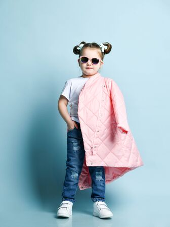 Cool stylish kid girl in white t-shirt, modern blue torn jeans and sunglasses is standing with long winter jacket on her shoulder
