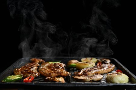 Hot Korean meat food preparation charcoal cooked with steam smoke bbq and vegetables on black background
