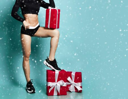 Sexy Christmas fitness sport woman body with perfect abs with new year 2020 gift box presents concept under snow on blue background Foto de archivo