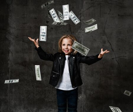 Happy lucky rich kid girl millionaire holding hands up under money rain throwing banknotes up catching money hundreds dollars cash on gray on dark concrete wall background