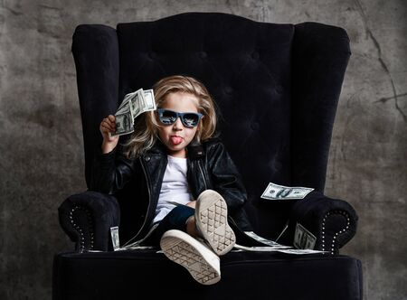Frolic rich kid girl in leather jacket and sunglasses is sitting in luxury armchair with a bundle of money dollars cash sticking her tongue out at us on concrete wall background Banco de Imagens