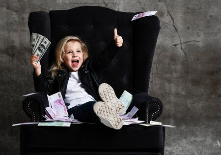 Happy lucky rich kid girl in leather jacket is sitting in luxury armchair with a bundle of money dollars cash showing thumb up sign gesture, screaming on concrete wall background Banco de Imagens